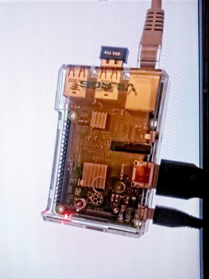 Wird nur in den seltensten Fällen so vor dem Fernseher hängen: Ein Raspberry Pi Model B vor seinem eigenen Desktop-Hintergrund.